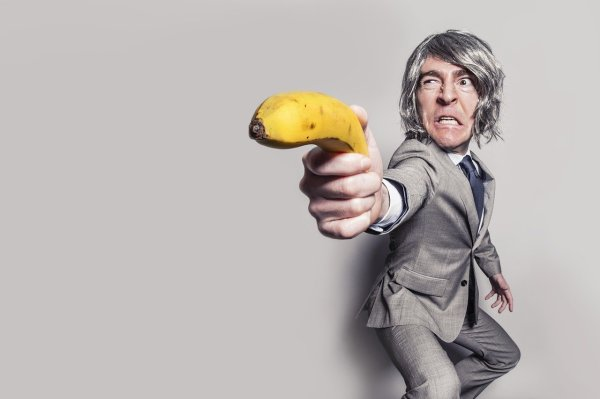 A man with a banana as a gun.